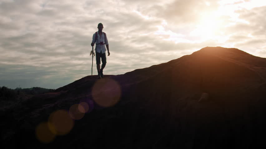 4k Hiker with walking stick and red backpack in desert mountain terrain at sunset.  | Shutterstock HD Video #23793301
