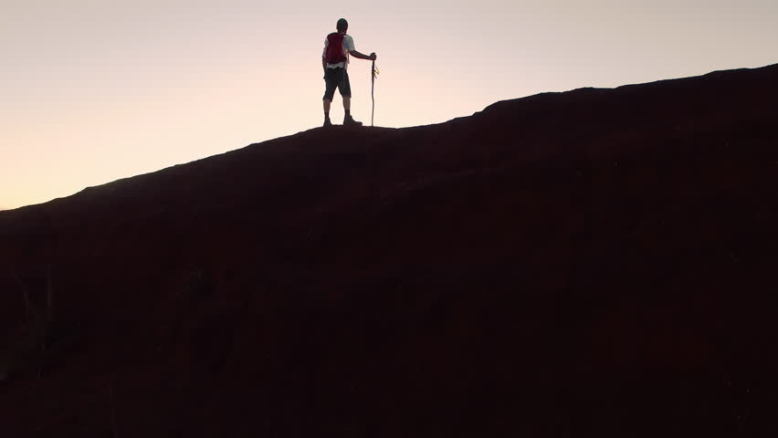 4k drone footage of hiker walking and drinking water with red backpack in desert mountain terrain at sunset.  | Shutterstock HD Video #23794936