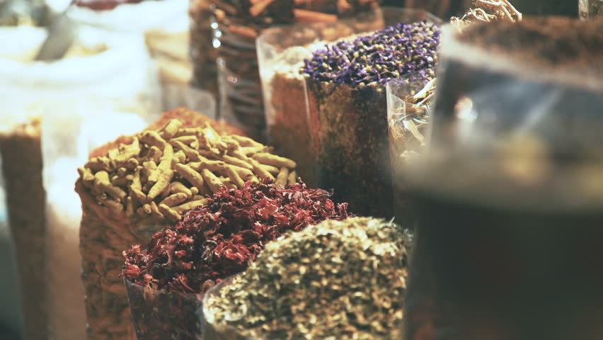Eastern Market with spices in Emirates. Hibiscus, curry, turmeric. Colourful and fragrant spices. The merchant market. Shop owner at spice market arranges display #23800264