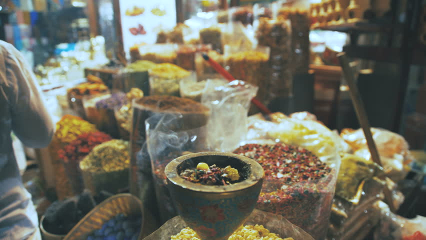 Eastern Market with spices in Emirates. Close-up of spices in different colors on the market in the UAE. Hibiscus, curry, turmeric. Shop owner at spice market arranges display #23800267