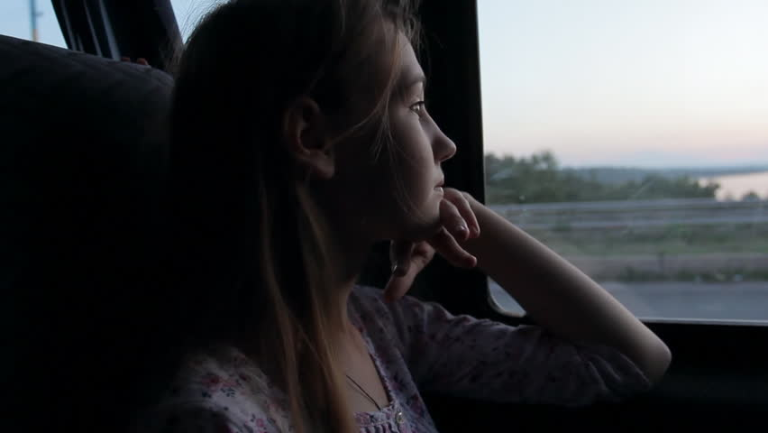 Sad pensive girl riding bus and looking out window at sunset