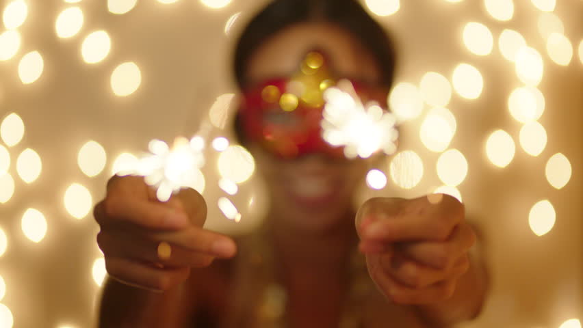 Beautiful young woman wearing carnival mask with bengal lights in her hands on New Year night | Shutterstock HD Video #23840974