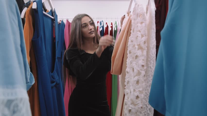 Portrait of a beautiful young brunette looking for a new dress at a fashion store and smiling | Shutterstock HD Video #23843698