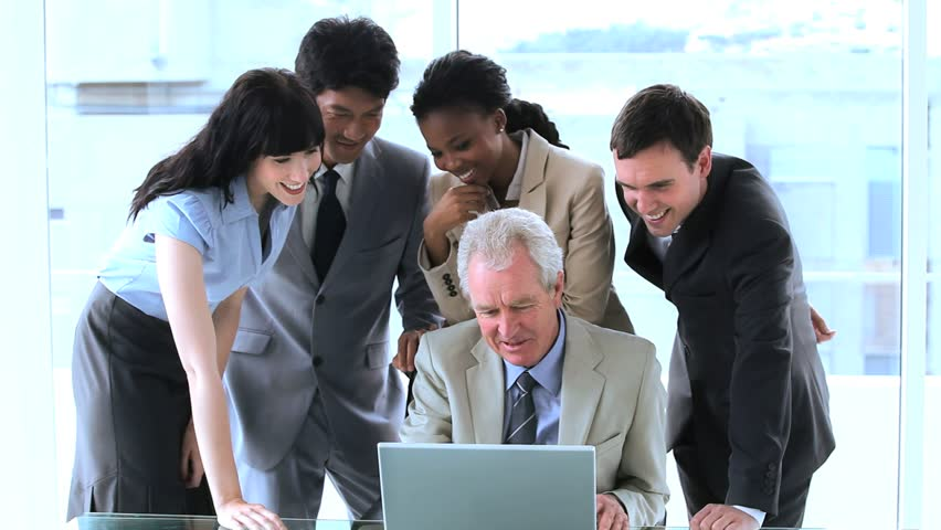 Smiling employees surrounding their manager in a bright room | Shutterstock HD Video #2384426