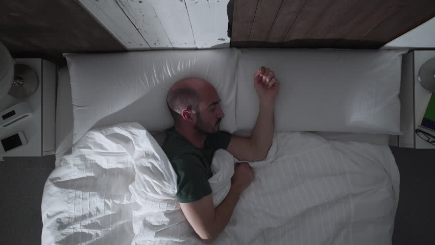 Young adult man can't sleep at night because of an irritating mosquito. He shakes his hand trying to get away the mosquito. Finally, he hides under the sheets. | Shutterstock HD Video #23847076