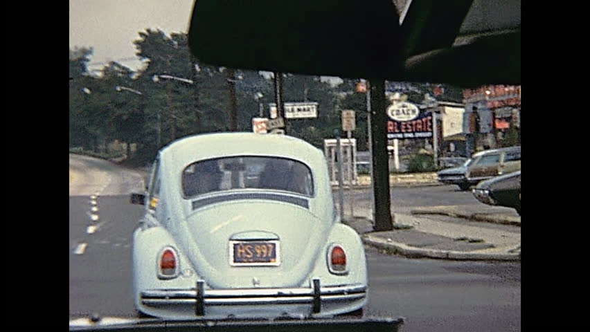 Bristol County, Massachusetts, United States of America - circa 1970: point of view tourist of driving car in Bristol County. Vintage cars on the road traffic in 70's.