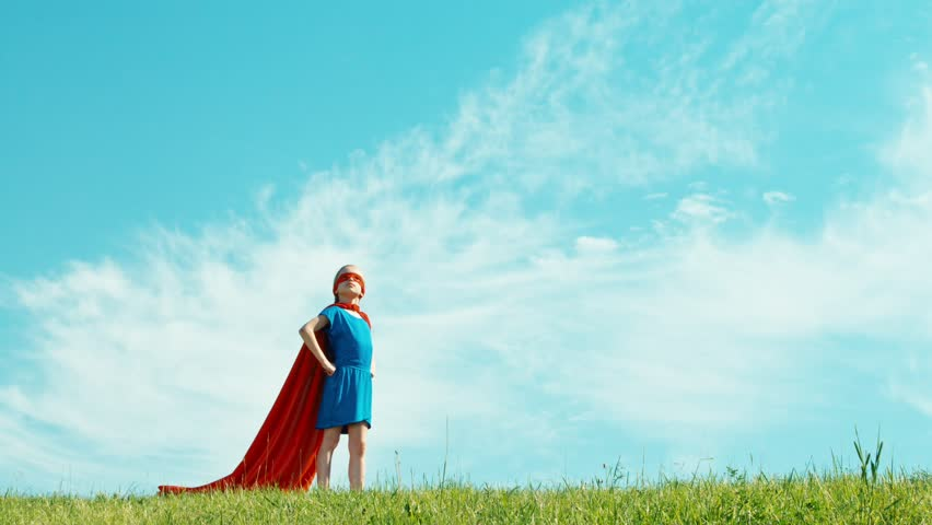 Super hero girl child 7-8 years old protects the world against the blue sky. Zooming