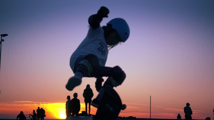 Silhouette of skater on skateboard jumping over sunset sky at Venice Beach skate park, California. Slow motion