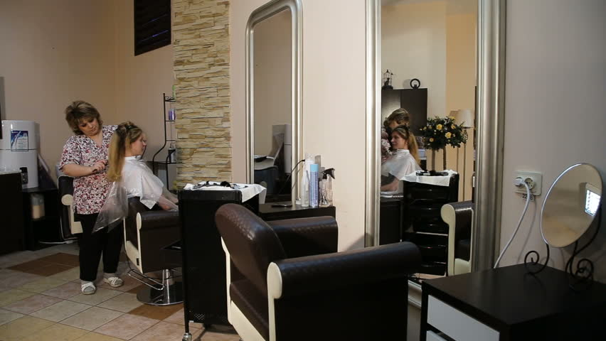Beautiful woman at the hairdresser blow drying her hair.Hairdresser drying long brown hair with hair dryer and round brush.Spa treatments, beauty center. In a the beauty salon. | Shutterstock HD Video #23876896