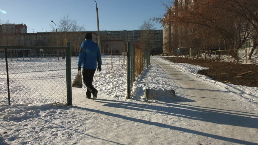 Winter. Walking man. A man in a blue jacket  with the package goes on a snow-covered track.
