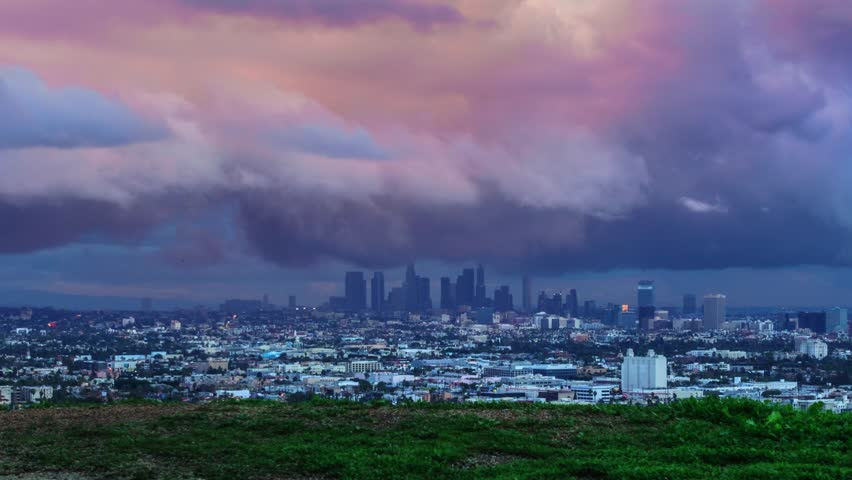 Epic storm clouds move over Los Angeles cityscape as dusk changes to night. City view from Hollywood Hills with downtown skyline in the background. 4K UHD timelapse.