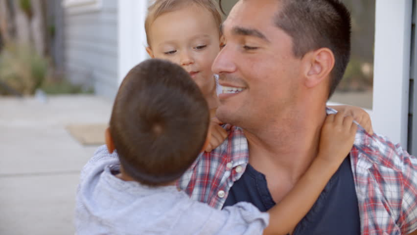 Father Hugging Children Sitting On Steps Outside Home