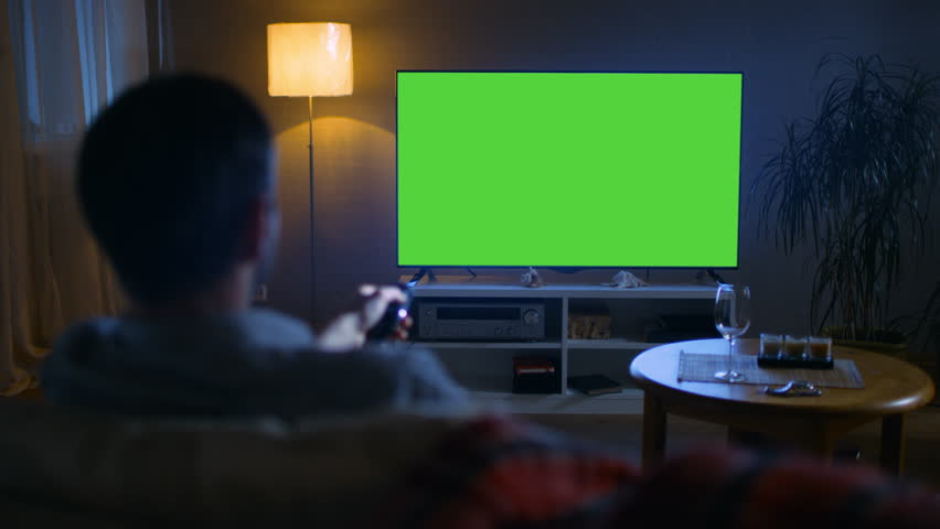 In the Evening Back View of a Middle Aged Man Sitting on a Couch Watching Big Flat Screen TV, He Switches Channels with Remote Control. It's Evening,  Shot on RED EPIC-W 8K Helium Cinema Camera. | Shutterstock HD Video #23884084