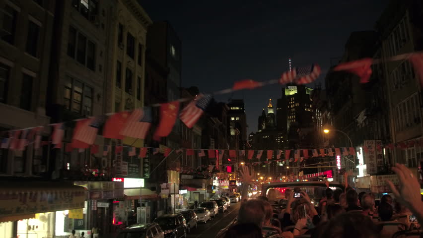 NEW YORK, USA - SEPTEMBER 23rd 2016: Tourists on night excursion driving in doble decker through colorful Chinatown adorned with traditional vibrant flag decorations and illuminated with neon signs   Shutterstock HD Video #23894098