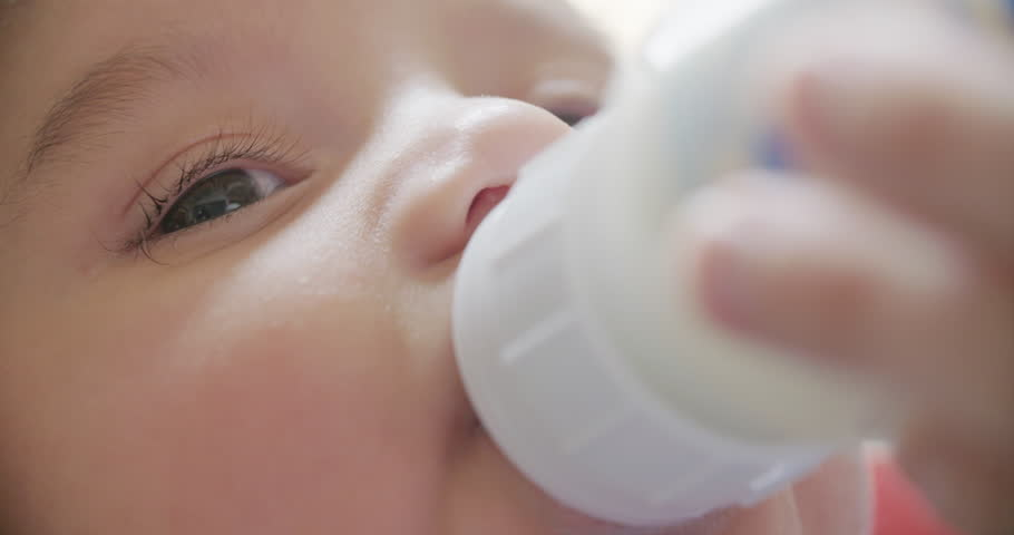 Baby Bottle Feeding Close Up Slow Motion. a slow motion close up of a 3 month old baby feeding from a bottle