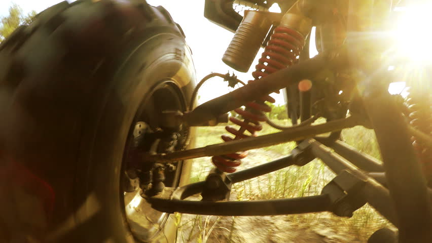 4K with sound : Shock-absorbers and a wheel of an ATV going through terrain