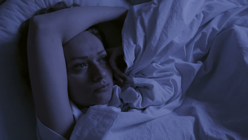 Insomnia concept. Woman in bed at night can not sleep