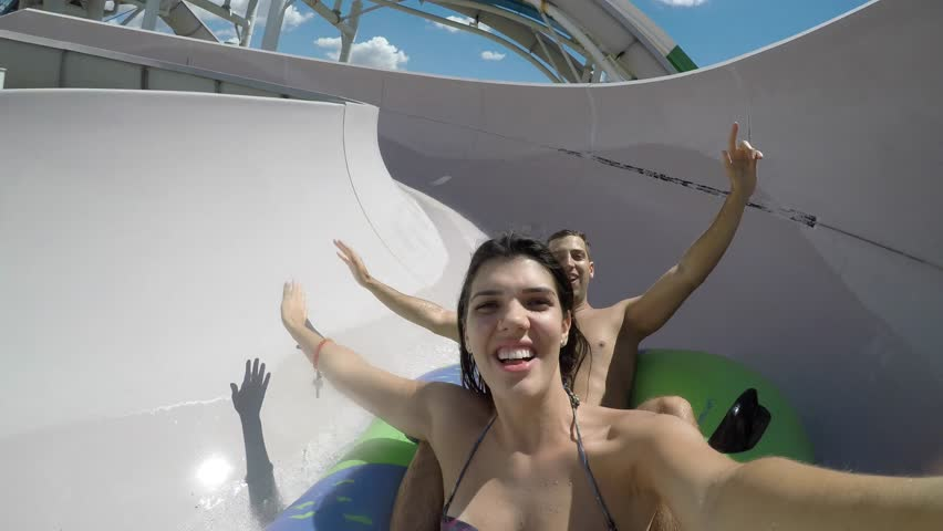 Couple having fun and sliding down in a water slide