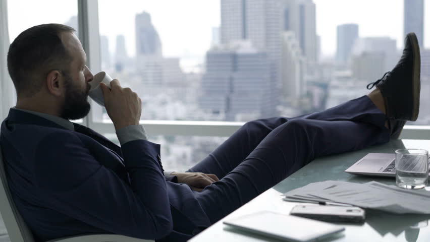 Young businessman relaxing, drinking water and admire view sitting by desk in office  #23967910
