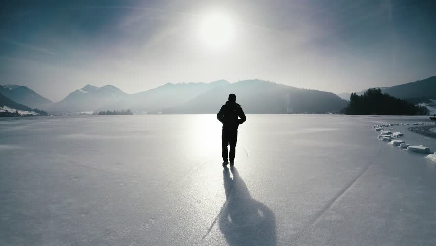 Lonesome man walking on frozen lake schliersee, bavaria, germany, near munich against mountains