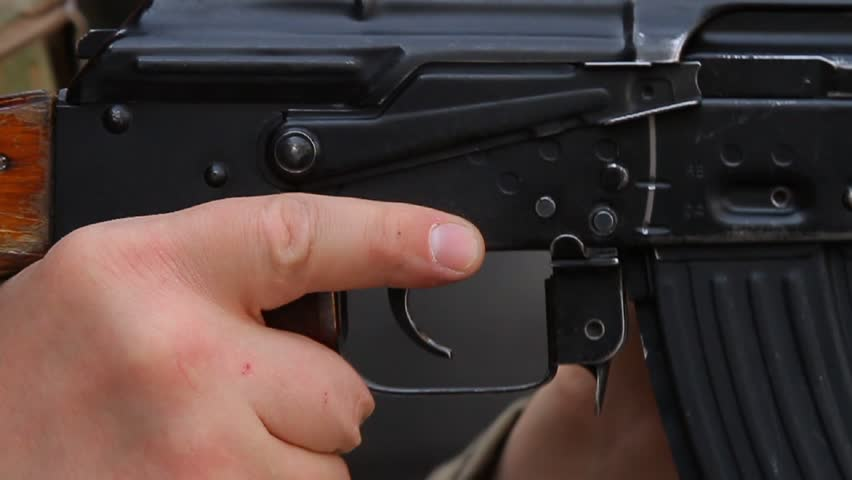 Closeup removal from safety lock, assault rifle, reloading and a finger on the trigger Kalashnikov assault rifle, three shots. / Removal from safety lock and shooting.