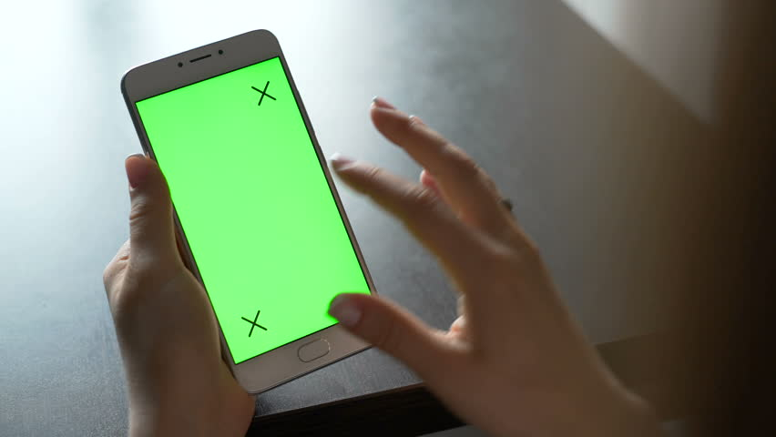 One person use cellular telephone with touch green screen for browsing social networks and communicating closeup. Girl, holding in hand portable gadget close up, as image of tech accessibility concept   Shutterstock HD Video #23974837