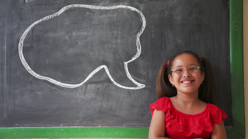 Concept on blackboard at school. Young people, student and pupil in classroom. Happy and funny latina girl in class. Portrait of female child smiling, looking at camera, saying words  | Shutterstock HD Video #23979070
