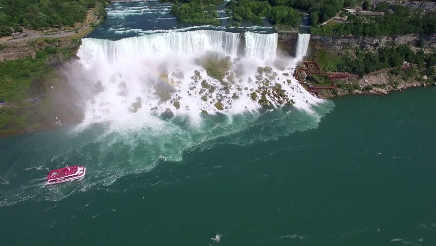Niagara Falls aerial view, Maid of the Mist tour boat passing in front of American Falls, one of three waterfalls that together are known as Niagara Falls, on the border of US and Canada.