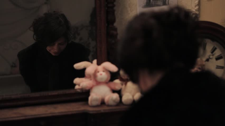 Sad brunette woman with hair knob in black clothes crying in front of reflection in mirror in bedroom with plush toys #24005746