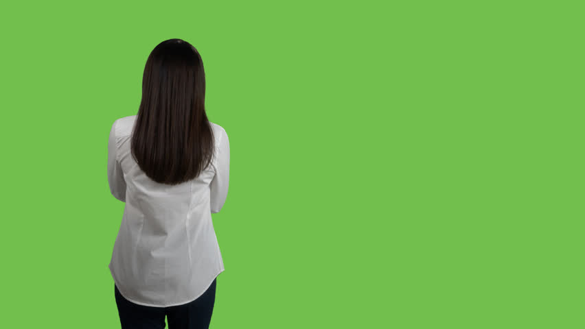 Rear view of woman in white shirt looking at something against green screen. 4k footage PNG with alpha channel