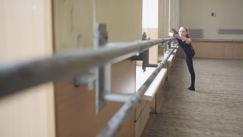 A young girl in tights stretching her leg at the barre | Shutterstock HD Video #24066448