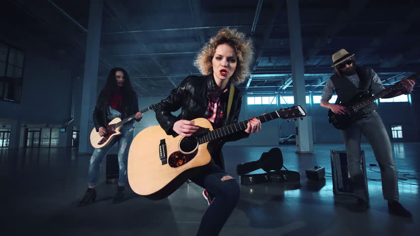 Curly haired woman in black jacket playing acoustic guitar in rock band, singing and dancing with her band members performing standing on sides, camera moving forward and back. Wide shot.
