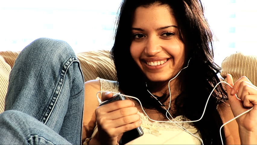 Beautiful latino girl relaxes at home with her mp3 player