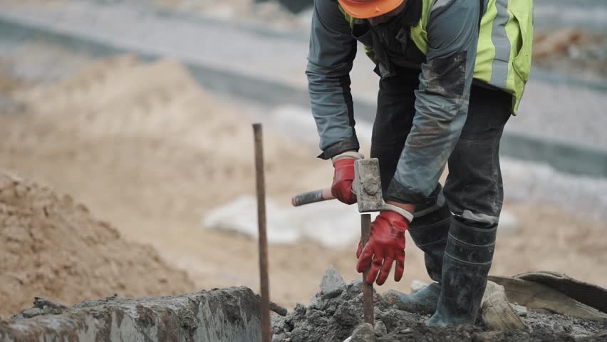 Slowmotion worker in red gloves hammering iron rod in to ground with sledgehammer