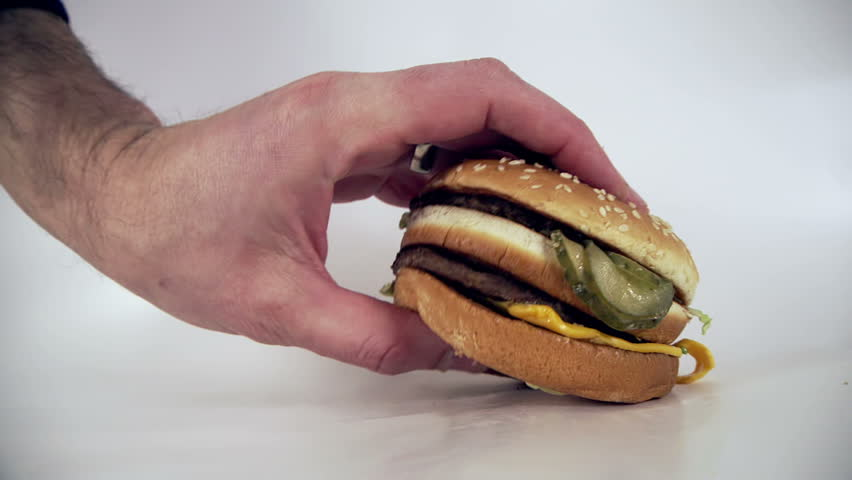 Male places down an unappetizing burger high in  cholesterol and saturated fats onto a white background | Shutterstock HD Video #24097309