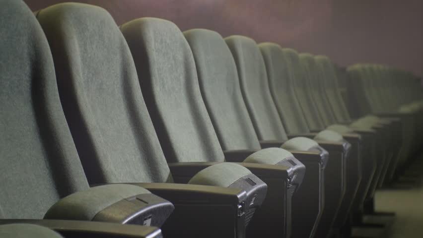 Closeup camera move along one row of empty gray soft chair in dark cinema hall | Shutterstock HD Video #24131242
