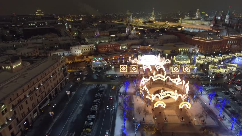 Flight above Theatre square and Red square. Beautiful Moscow city Christmas night illumination. Happy people walk. Aerial drone 4K footage. Winter.