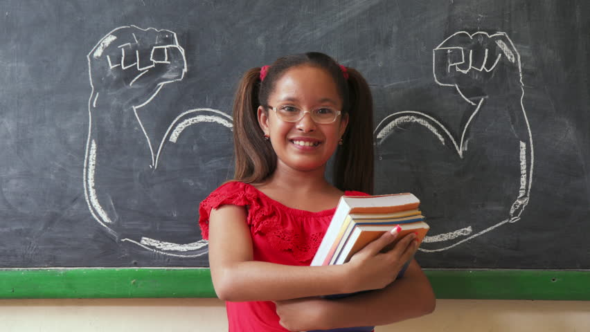 Concept on blackboard at school. Young people, student and pupil in classroom. Intelligent and successful hispanic girl in class. Portrait of female child smiling, looking at camera, holding books  Royalty-Free Stock Footage #24132550