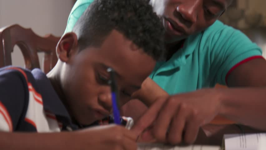 Happy black family at home. African american father and child. Latino dad helping son with school homework. Education and relationship, man teaching and boy learning