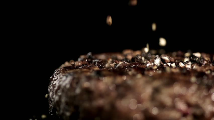 MACRO FOOD: small pieces of pepper falling juicy steak in slow motion