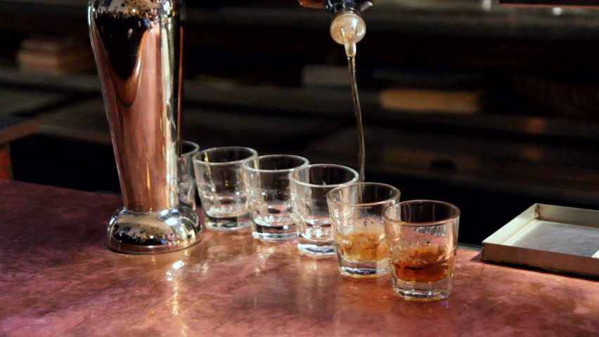 Bar tender pouring whiskey into six shot glasses. | Shutterstock HD Video #2413691