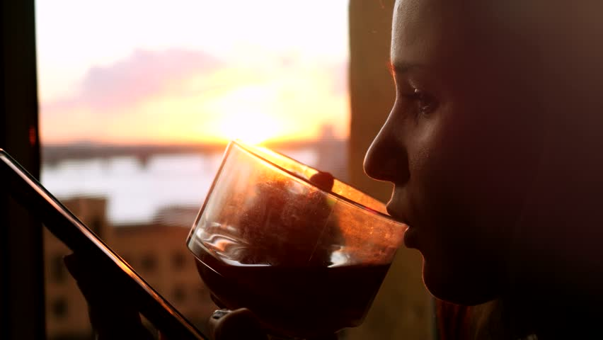 Young woman uses the phone, standing at the window drinking coffee on the background of a beautiful sunset with sun flare. 3840x2160. 4k | Shutterstock HD Video #24150892