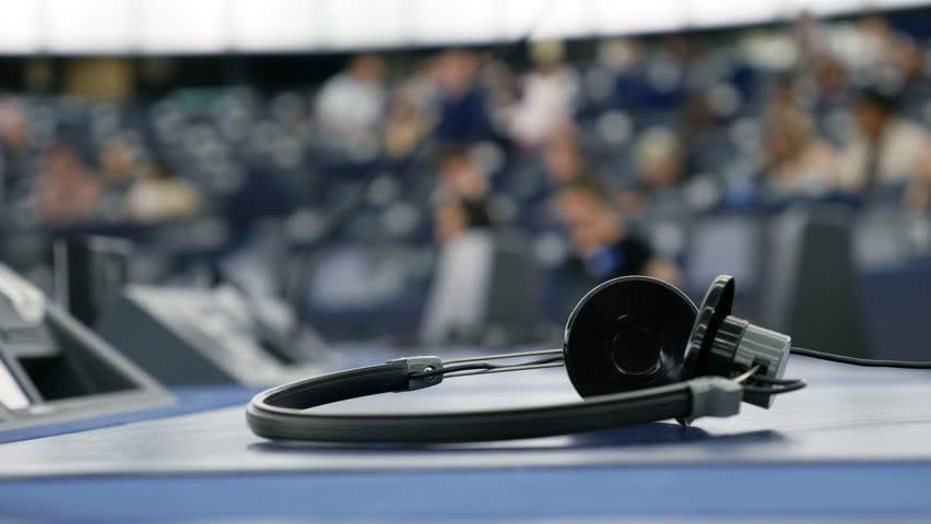 Headphones used for simultaneous translation equipment (simultaneous interpretation equipment or synchronous translation) inside European Parliament debate room  Royalty-Free Stock Footage #24165616