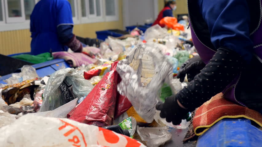 Workers sorting garbage, waste to be processed in a recycling plant. Enviroment protection concept. | Shutterstock HD Video #24176854