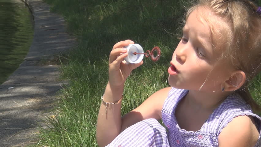 A Cute Blonde Little Girl playing with Soap Bubbles, Outdoor Having Fun