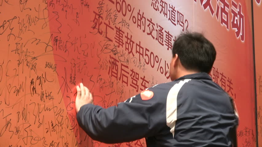 QINGDAO - MAY 11: People are writing their signature on a banner for an anti Drink & Drive campaign on May 11, 2010 in Qingdao, China