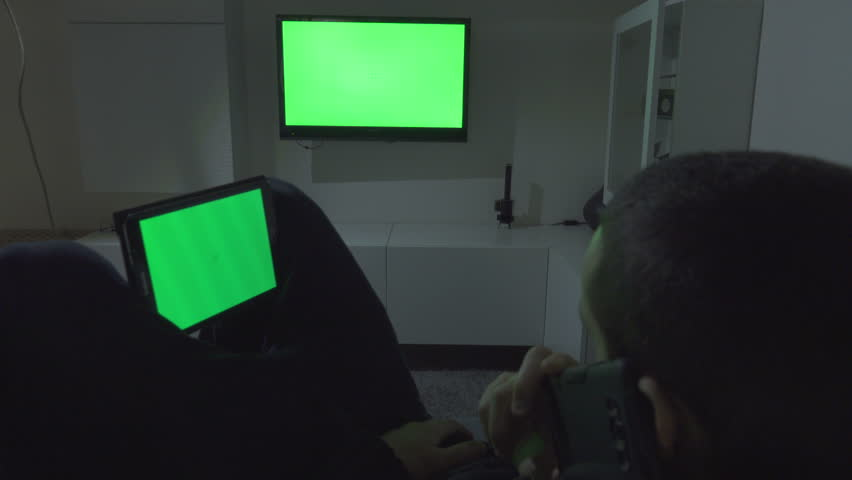 Young Man Using Tablet, Tv and Smartphone. Green Screen #24199657