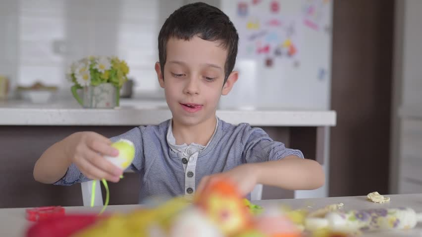 Young boy playing with dough and Easter eggs at home #24206452