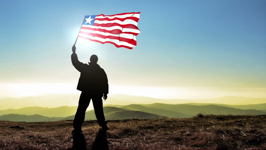 Successful silhouette man winner waving Liberia flag on top of the mountain peak, Cinemagraph LOOP background #24223015