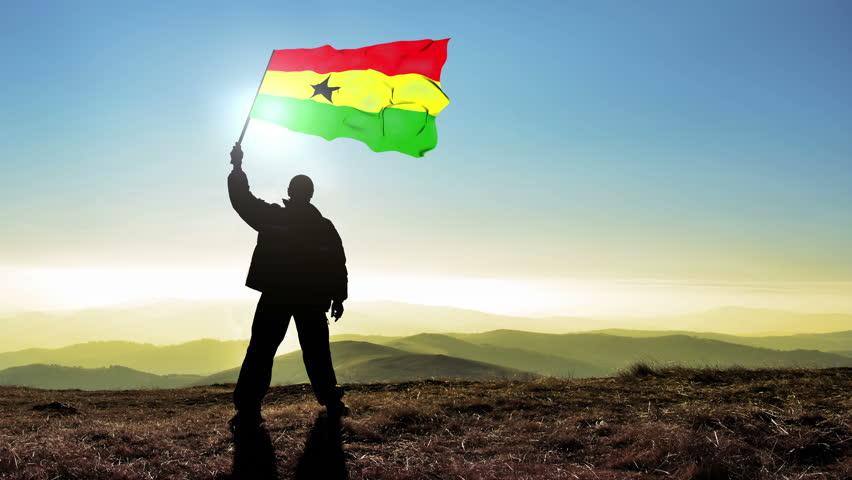 Successful silhouette man winner waving Ghana flag on top of the mountain peak. Cinemagraph LOOP background | Shutterstock HD Video #24223027